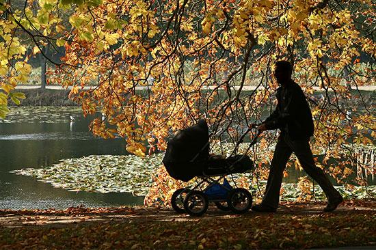 Far går med barnevogn i parken